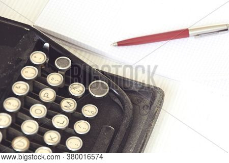 An Old Black Typewriter Next To A White Sheet Of Paper With A Red Pen. Journalism And Writing Tools.