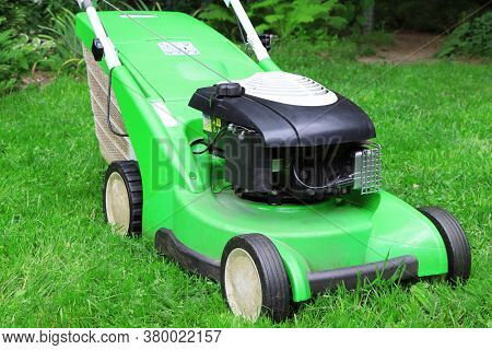 A Green Lawnmower In The Garden. A Lawn Mower On The Green Grass. Gardening.