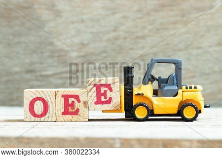 Toy Forklift Hold Letter Block E To Complete Word Oee (abbreviation Of Overall Equipment Effectivene