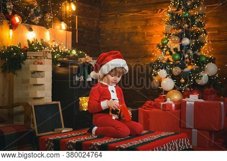 Funny Kid Holding Christmas Gift. Child With Gift. Models Child Having Fun With Gift. Kid Having Fun