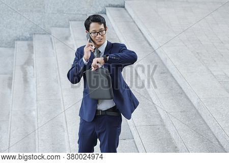 Handsome Positive Young Asian Entrepreneur Checking Time On His Wristwatch When Talking On Phone Wit
