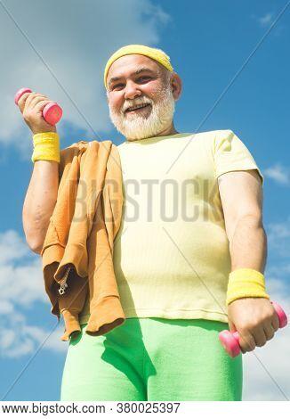 Rehabilitation Center For Elderly Aged Pensioner. Senior Sport Man Lifting Dumbbells In Sport Center