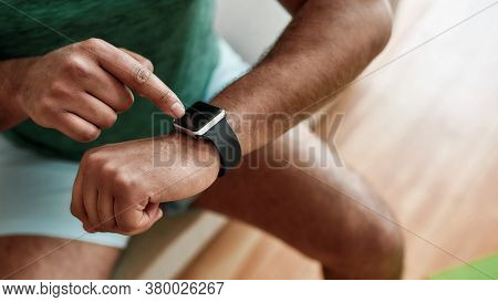 Technology. Close Up Of Hands Of Active Man Checking Time, Using Smartwatch While Doing Morning Work