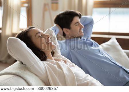 Peaceful Smiling Millennial Spouses Daydreaming Relaxing At Home.
