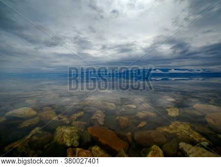 Lake Baikal In Summer Before A Thunderstorm With Colorful Stones Under Transparent Water