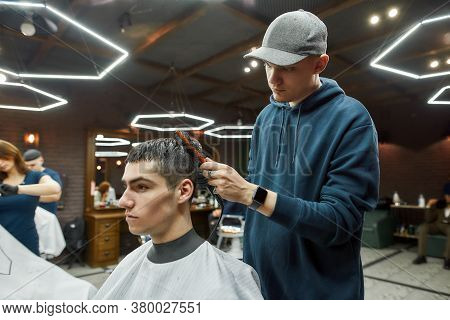 Getting Trendy Haircut. Side View Of A Professional Barber Drying The Hair Of A Handsome Guy In The