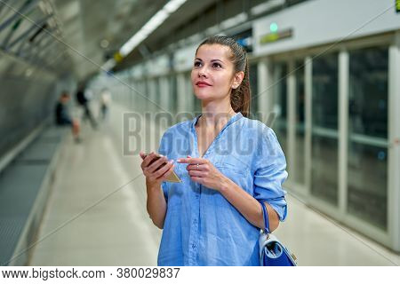 Young Woman Using Cell Phone In Subway Station Waiting For The Arrival Of Train