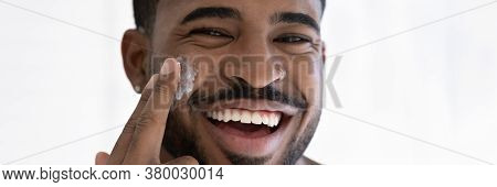 Close Up Overjoyed African American Man Applying Moisturizing Face Cream
