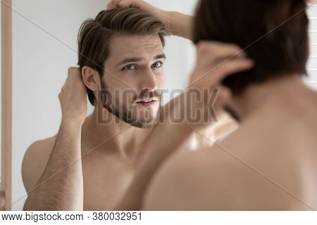 Close Up Anxious Young Man Touching Hair, Looking In Mirror