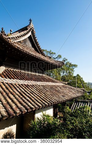 Wooden Carved, Decorated Roofs Of Buddhist Temple In Nagasaki, Japan Among Green Trees.