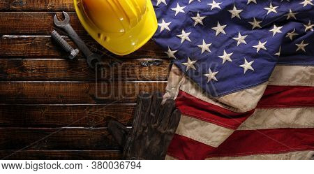 Hardhat, gloves, and tools on US American flag. Strong American workforce or industry, or America labor day concept.