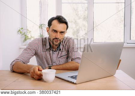 A Man Drinking Coffee And Working On A Laptop At The Table