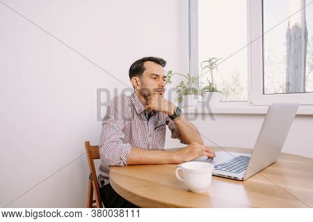 Man In Shirt With A Cup Of Coffee Works On Laptop