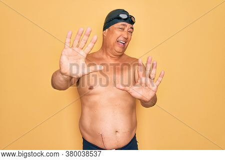 Middle age senior grey-haired swimmer man wearing swimsuit, cap and goggles afraid and terrified with fear expression stop gesture with hands, shouting in shock. Panic concept.