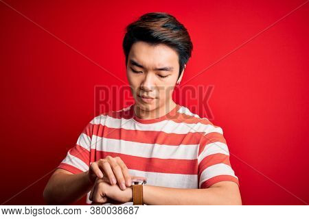 Young handsome chinese man wearing casual striped t-shirt standing over red background Checking the time on wrist watch, relaxed and confident