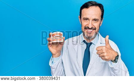 Middle age handsome dentist man wearing coat holding plastic teeth with brackets smiling happy and positive, thumb up doing excellent and approval sign