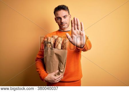 Young handsome man holding paper bag with bread over isolated yellow background with open hand doing stop sign with serious and confident expression, defense gesture