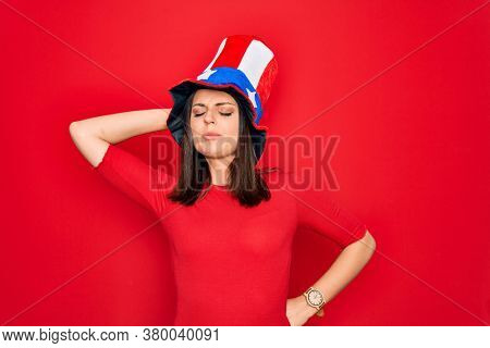 Young beautiful brunette woman wearing united states hat celebrating independence day Suffering of neck ache injury, touching neck with hand, muscular pain