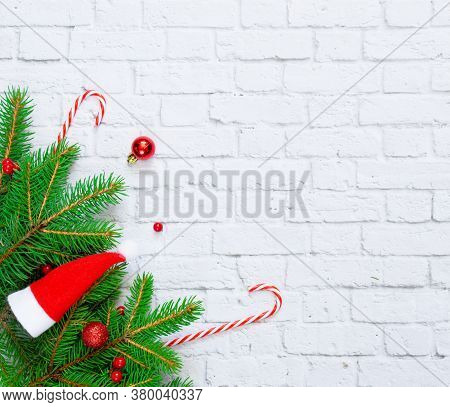 Christmas Composition. Fir Tree Branches, Sweet Red Canes, Red Christmas Balls On White Concrete Bac