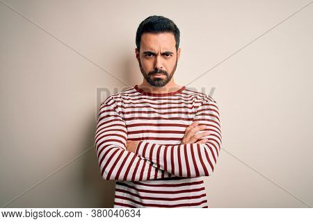 Young handsome man with beard wearing casual striped t-shirt standing over white background skeptic and nervous, disapproving expression on face with crossed arms. Negative person.
