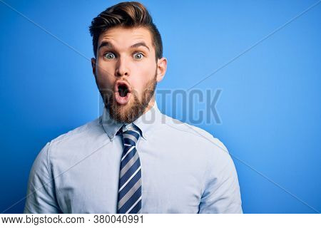 Young blond businessman with beard and blue eyes wearing elegant shirt and tie standing afraid and shocked with surprise expression, fear and excited face.