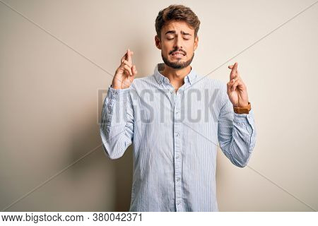 Young handsome man with beard wearing striped shirt standing over white background gesturing finger crossed smiling with hope and eyes closed. Luck and superstitious concept.