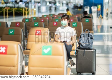 Young Female Wearing Face Mask And Sitting On Chair In In Airport, Protection Coronavirus Disease (c