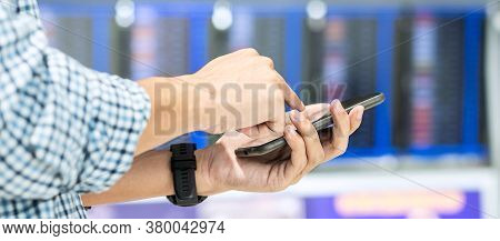 Casual Businessman Using Smart Phone At Flight Information Board In Airport Terminal, Hipster Male T