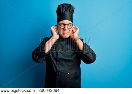 Middle age handsome grey-haired chef man wearing cooker uniform and hat covering ears with fingers with annoyed expression for the noise of loud music. Deaf concept.