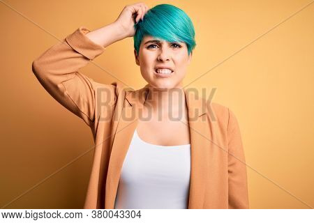 Young beautiful woman with blue fashion hair wearing casual jacket over yellow background confuse and wonder about question. Uncertain with doubt, thinking with hand on head. Pensive concept.