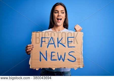Young beautiful brunette woman holding banner with fake news message pointing and showing with thumb up to the side with happy face smiling