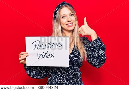 Young blonde woman holding positive vibes banner smiling happy and positive, thumb up doing excellent and approval sign