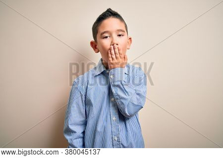 Young little boy kid wearing elegant shirt standing over isolated background bored yawning tired covering mouth with hand. Restless and sleepiness.