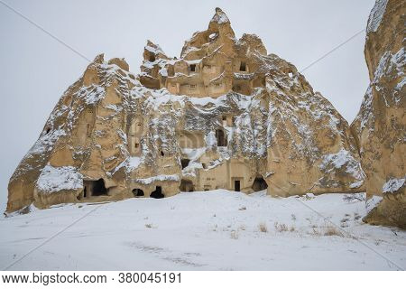 Solitary Rock With Ancient Dwellings On A Cloudy January Day. Cappadocia