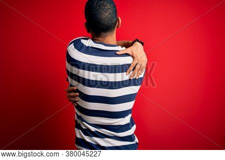 Handsome african american man wearing casual striped t-shirt standing over red background Hugging oneself happy and positive from backwards. Self love and self care