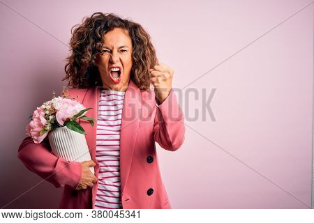 Middle age beautiful woman holding vase with flowers over isolated pink background annoyed and frustrated shouting with anger, crazy and yelling with raised hand, anger concept