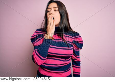 Young brunette elegant woman wearing striped shirt over pink isolated background bored yawning tired covering mouth with hand. Restless and sleepiness.