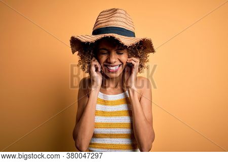 African american tourist woman with curly on vacation wearing summer hat and striped t-shirt covering ears with fingers with annoyed expression for the noise of loud music. Deaf concept.
