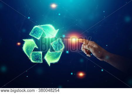 Recycling Hologram Sign On A Blue Background. Green Eco Recycling Symbol And Human Hand. The Concept