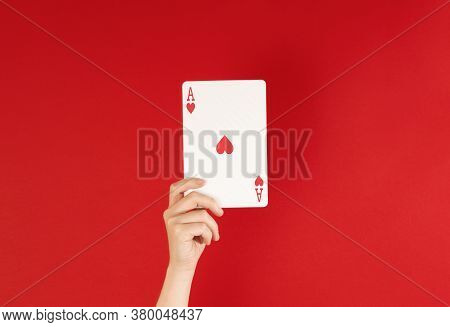 Ace Of Hearts, Hand Holding Up Playing Card Against A Deep Red Background, With Copy Space