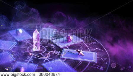 Cartomancy - Pendulum On Blurred Altar With Defocused-tarot Cards And Smoke