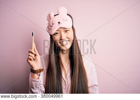 Young beautiful asian woman wearing pajama brushing her teeth using tooth brush and oral paste, cleaning teeth and tongue as healthy health care morning routine