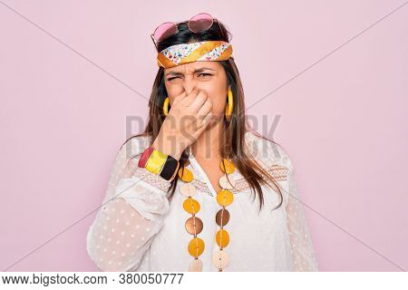 Young hispanic hippie woman wearing fashion boho style and sunglasses over pink background smelling something stinky and disgusting, intolerable smell, holding breath with fingers on nose. Bad smell