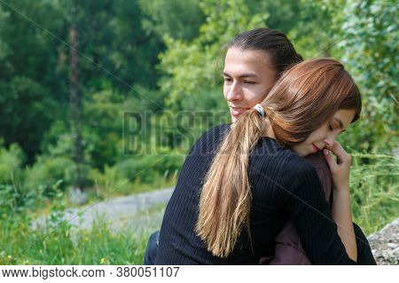 A Man Of Asian Appearance Embraces A Young Woman Of European Appearance. International Love Of Heter
