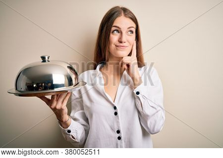Young beautiful redhead woman holding waitress tray over isolated white background serious face thinking about question, very confused idea