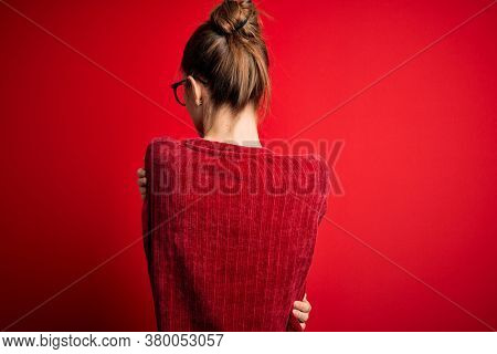 Young beautiful redhead woman wearing casual sweater over isolated red background Hugging oneself happy and positive from backwards. Self love and self care