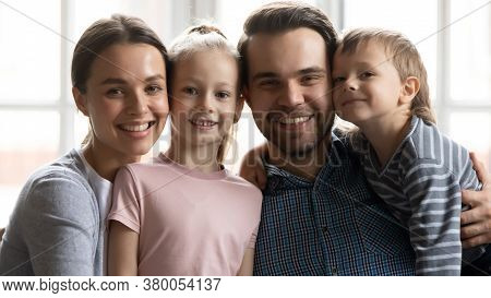 Portrait Of Happy Young Parents Cuddling Kids.