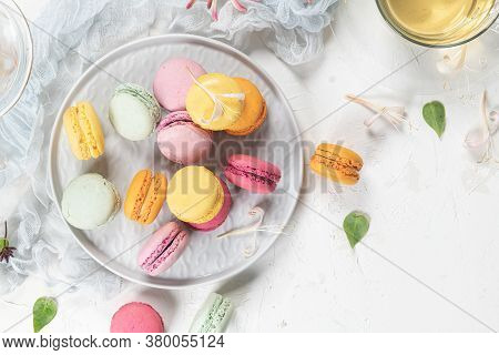 Colorful French Macaroon Cakes. Macaroons With Jasmine Flowers And Tea On White Table Background. Se