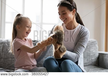 Overjoyed Little Girl Playing Hand Toys With Loving Young Mother.