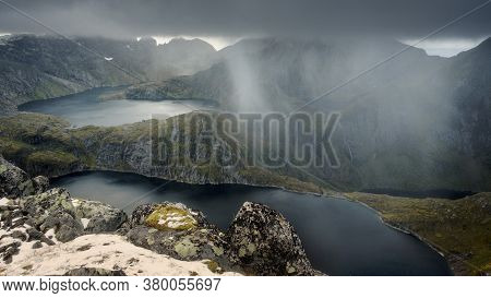 Rain And Thunderclouds In The Mountains Of Norway Before The Storm. Dramatic Landscape Of Lakes, Pea